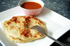 Roti Canai. Malaysian style 'roti' served on white plate and curry stock photo