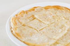Roti Canai häller förtätat mjölkar och strilar socker överst, klippte int Arkivbild
