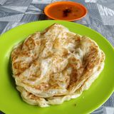 Roti canai. Malaysian style & x27;roti& x27; served on green plate and curry Stock Image