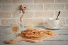 Roti, a cup of coffee and a glass of tea are on the table in white background. Food scenery roti, coffee cup and a glass of tea in white background Royalty Free Stock Images
