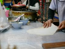 Roti dough being stretched and slapped into a sheet before being fried in hot griddle stock photos
