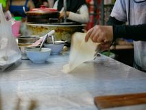 Roti dough being stretched and slapped into a sheet before being fried in hot griddle stock photography