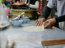 Roti dough being stretched and slapped into a sheet before being fried in hot griddle stock image