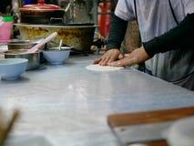 Roti-Teig massierend und in ein Blatt ausgedehnt worden, bevor im heißen Bratpfanne gebraten werden lizenzfreie stockfotos