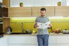 Rotina diária do homem do licenciado jornal da leitura do conceito do estilo de vida da cozinha no único imagens de stock royalty free