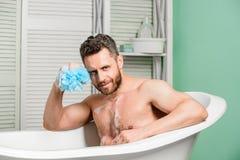 Rotina mimar e de beleza Banheira de relaxamento do homem muscular consider?vel Conceito morno do banho Transforme seu banheiro e fotos de stock