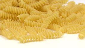 Pasta Rotini Fill. Rotini pasta falling on white background and filling the screen in slow motion stock video