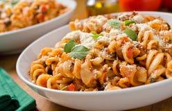 Rotini with tomato sauce and oregano. A setting of rotini pasta with tomato sauce, parmesan cheese, olive oil, and fresh oregano stock photo