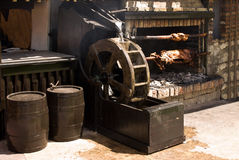 Rotisserie with the meet. Rotisserie with pig and chicken over the coals, spinning by water wheel Stock Photography