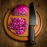 Rotkohl schnitt Scheibe mit Küchenmesser auf Holz des hackenden Brettes Lizenzfreies Stockfoto