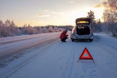 Roto en un camino nevoso del invierno fotografía de archivo