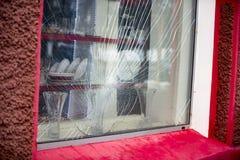 Roto por el escaparate de protesta de los manifestantes foto de archivo