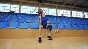 Rotolamento del disabile una palla mentre sedendosi ad un campo da pallacanestro, protesi bionica archivi video