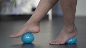 Rotolamento della donna che massaggia avanti e indietro palla con il piede, piedi di analgesico archivi video