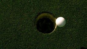 Rotolamento della palla da golf nel foro su verde mettente video d archivio