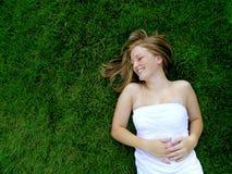 Rotolamento della ragazza nell'erba Fotografie Stock Libere da Diritti