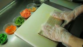 Rotolamento su del rotolo di sushi con il tobiko rosso e verde video d archivio