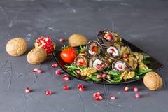 Rotoli arrostiti delle melanzane con i dadi, formaggio, aglio ed erbe, su un fondo grigio, piatto georgiano immagine stock