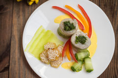 Rotoli del pesce avvolti in zucchini con le patate arrostite spruzzate con i semi di sesamo e le fette di peperone dolce e di cet Immagini Stock Libere da Diritti