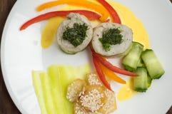Rotoli del pesce avvolti in zucchini con le patate arrostite spruzzate con i semi di sesamo e le fette di peperone dolce e di cet Immagini Stock