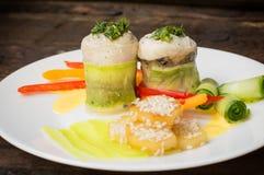Rotoli del pesce avvolti in zucchini con le patate arrostite spruzzate con i semi di sesamo e le fette di peperone dolce e di cet Fotografia Stock