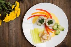 Rotoli del pesce avvolti in zucchini con le patate arrostite spruzzate con i semi di sesamo e le fette di peperone dolce e di cet Immagine Stock Libera da Diritti