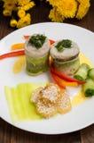 Rotoli del pesce avvolti in zucchini con le patate arrostite spruzzate con i semi di sesamo e le fette di peperone dolce e di cet Immagine Stock