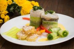 Rotoli del pesce avvolti in zucchini con le patate arrostite spruzzate con i semi di sesamo e le fette di peperone dolce e di cet Fotografia Stock Libera da Diritti