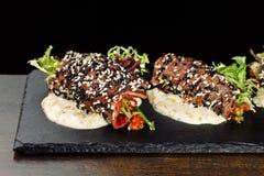 Rotoli di salsiccia casalinghi sull'ardesia nera fotografia stock