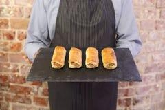 Rotoli di salsiccia della tenuta dell'uomo fotografie stock