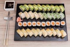 Rotoli di sushi, causa, California, tempura con la salsa di soia su una tavola di legno immagini stock