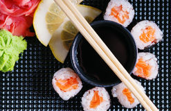 Rotoli di sushi con il salmone, la salsa di soia ed i bastoncini Fotografia Stock Libera da Diritti