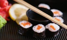 Rotoli di sushi con il salmone, la salsa di soia ed i bastoncini Fotografia Stock