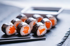 Rotoli di sushi con il salmone, la salsa di soia ed i bastoncini Immagini Stock