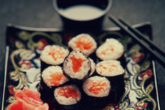 Rotoli di sushi con il salmone, la salsa di soia ed i bastoncini Fotografie Stock Libere da Diritti