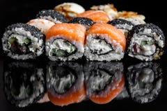 Rotoli di sushi con il salmone, il tonno, il cetriolo e le cipolle verdi su fondo nero fotografia stock