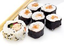 Rotoli di sushi deliziosi sulla zolla bianca con i bastoncini Fotografie Stock Libere da Diritti