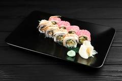 Rotoli di sushi giapponesi freschi tradizionali su un fondo nero Fotografia Stock