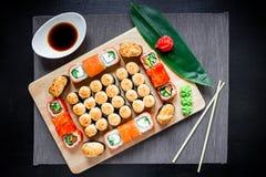 Rotoli di sushi, salsa di soia, zenzero e bastoncini giapponesi su una tavola scura Vista superiore Disposizione piana Alimento t Fotografia Stock Libera da Diritti
