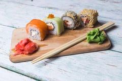 Rotoli di sushi su un bordo di legno Immagini Stock