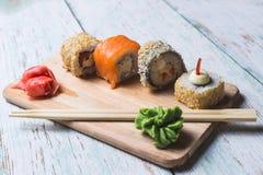 Rotoli di sushi su un bordo di legno Fotografie Stock Libere da Diritti