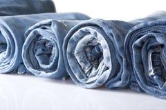 Rotoli i jeans blu del denim organizzati nella riga Immagine Stock Libera da Diritti