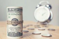 Rotoli la banconota del dollaro dei soldi con le monete e cronometri sulla tavola, Americ Immagine Stock