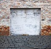 Rotoli in su il portello del garage sul muro di mattoni Fotografia Stock