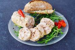 Rotolo casalingo del pollo con le spezie su una lastra di vetro su un fondo astratto grigio Cibo sano della prima colazione sana fotografia stock