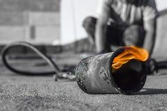 Rotolo che copre installazione con la torcia per saldature del propano durante i lavori di costruzione immagini stock libere da diritti