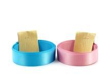 Rotolo dei nastri variopinti blu e rosa con le cinghie dell'etichetta della carta dell'oro isolate su fondo bianco Fotografia Stock