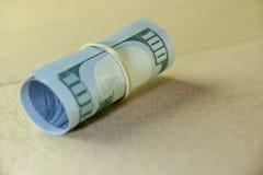 Rotolo dei soldi con la banconota in dollari di nuovo cento degli Stati Uniti Immagini Stock Libere da Diritti