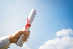 Rotolo del certificato di graduazione della tenuta della mano nell'ambito del sole, blu immagini stock libere da diritti