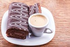 Rotolo del cioccolato con una tazza di caffè Fotografia Stock